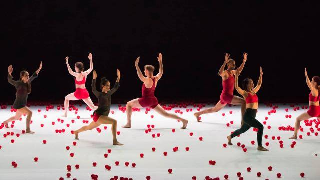 dancers on the stage floor surrounded by red balls, with one standing dancer in a passé position.