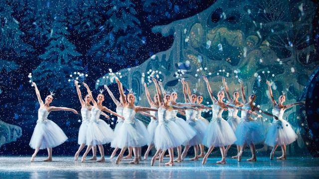 ballet dancers in long white tutu on a winter forest background with snow falling