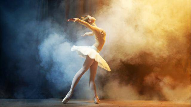 Ballerina in a white tutu posing sideways with leg extended in a tendu derrière position, slightly arched back with arms side, on a background of thick smoke.