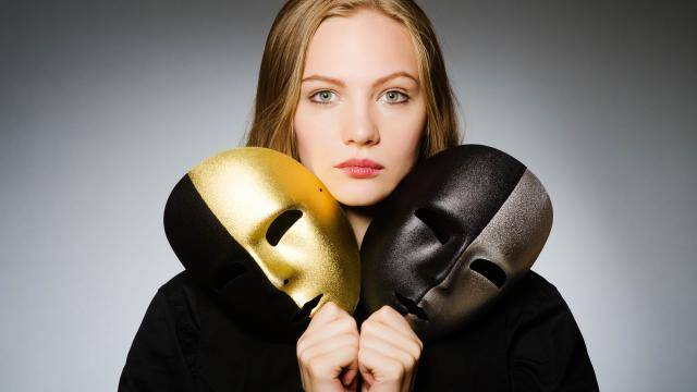 Young woman holding gold silver and black theatre masks
