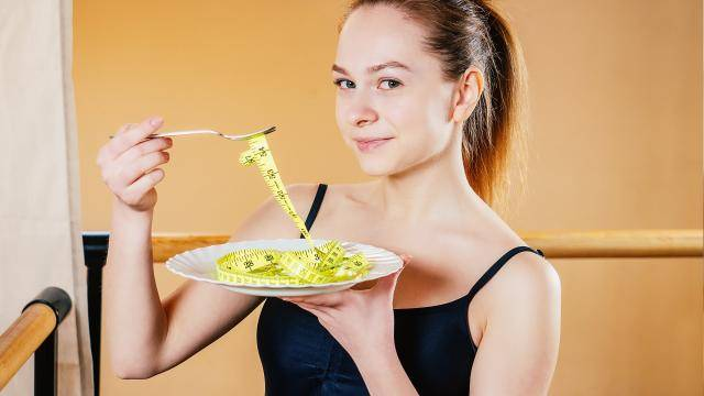 woman in a dance studio, holding a plate with a yellow measuring tape as if it was pasta