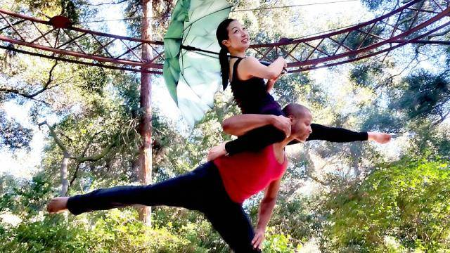 Outdoors surrounded by trees, male dancer in an arabesque lifting a female dancer on his shoulders as she is holding a green umbrella.