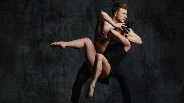 Female dancer struggling out of a male dancer's grip as he holds her head