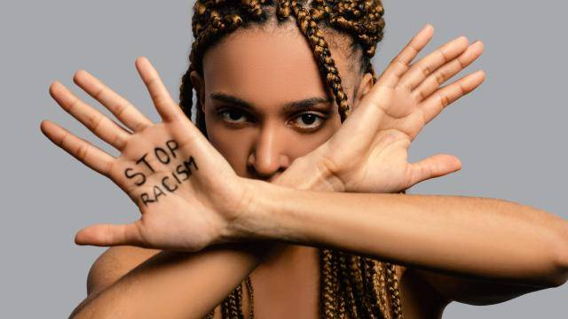 """young Black woman with dreads, holding her arms crossed in front of her face, palms open, with """"stop racism"""" written on one palm"""