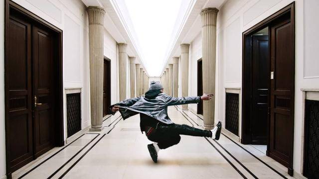 Male hip-hop dancer in the middle of a long hallway, pointing at an open door.