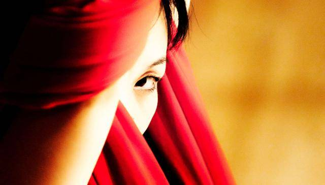 Close up of Cinder Che's eye behind a red scarf