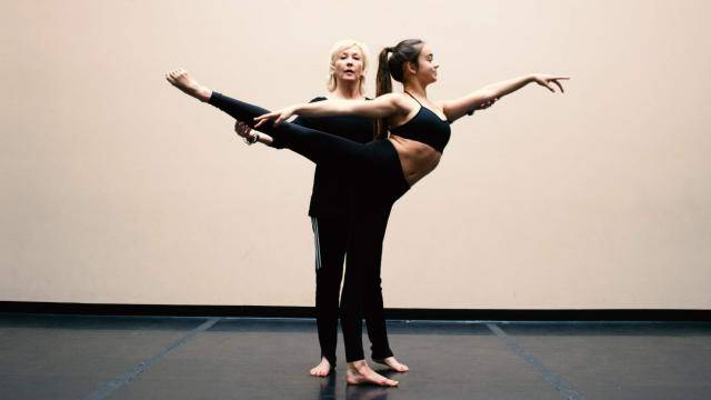 Paula Kessinger aligning one of her students in an arabesque position