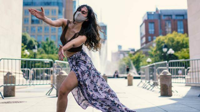 Dancer Gianna Bartolini with a mask reaching her arms out in a fenced street