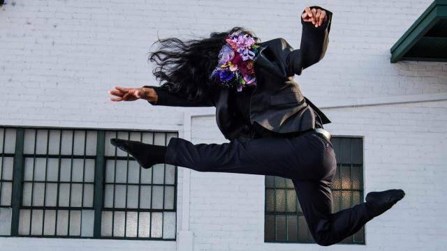Dancer Shu Kinouchi with a flowered cover on her face jumping in front of a white brick wall