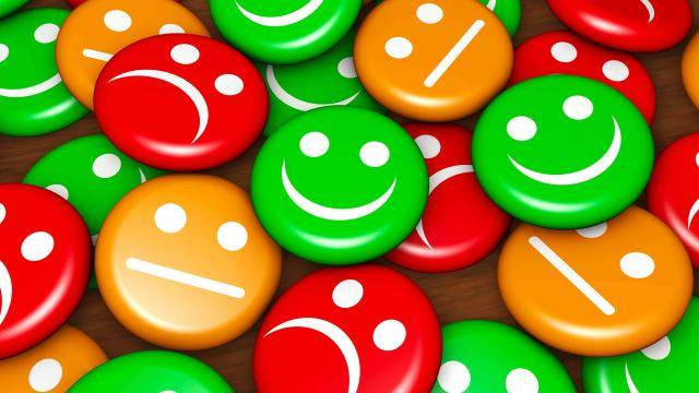 A pile of small colorful disks with expressions: green ones smiling, orange ones neutral, and red ones unhappy.