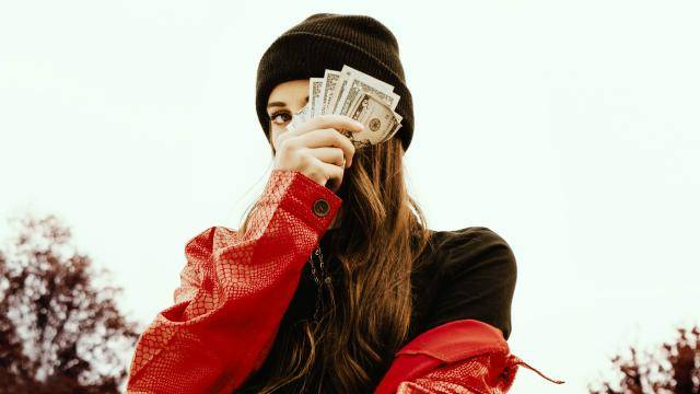 woman with black beanie and red leather jacket holding money in front of her eye