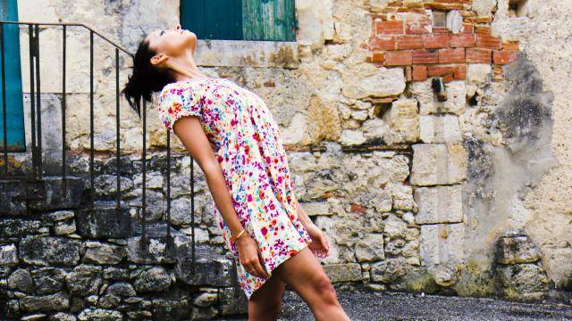 young woman in a flower dress looking up in a rural street