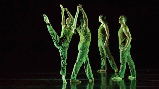 a male dancer holding a female dancer with leg high in front, 2 other dancers behind