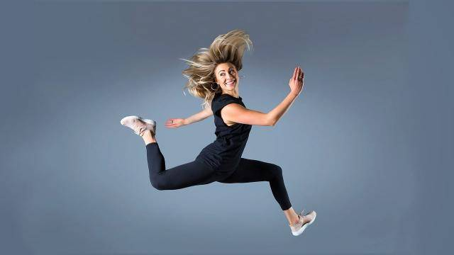 Lauren Ritchie leaping and looking back on a grey background.