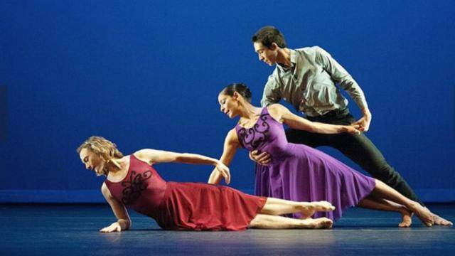 A male dancer holding a female dancer in a purple dress as she is leaning over behind another female dancer in a red dress laying on her side on the floor.