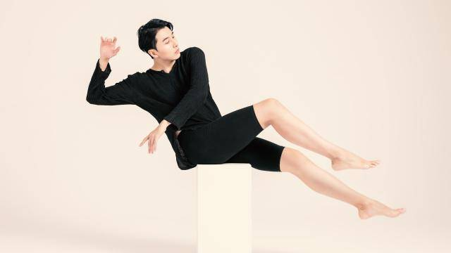 asian male dancer in black leaning back on a white stool