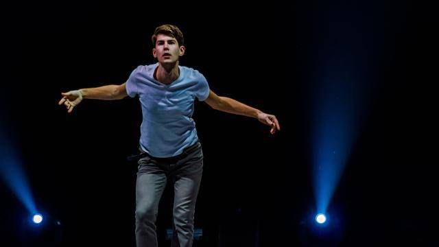 Male dancer in a bue shirt performing alone on a dark stage with blue lighting.