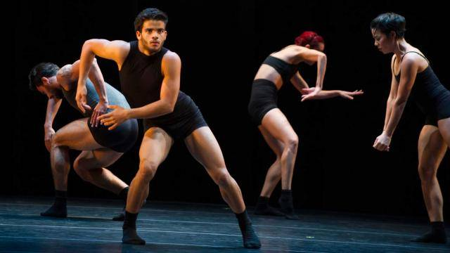 4 dancers on stage in black tops and shorts in different posing and  facing different directions.