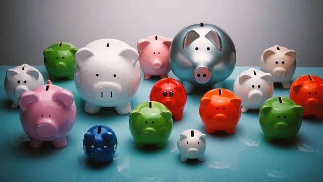 A group of piggy banks of various sizes and colors.