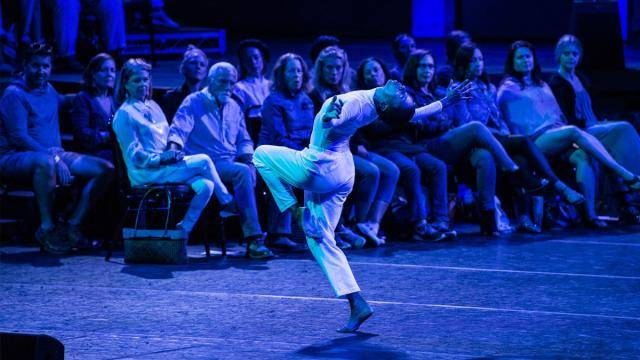 Dancer Mecca Romero, in white top and pants,  doing a passé arching back in front of 2 rows of audience sitting on chairs on the performance stage.