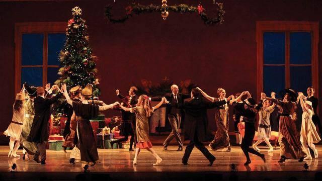 A group of children and adult dancing in circle holding hands in front of a big Christmas tree.