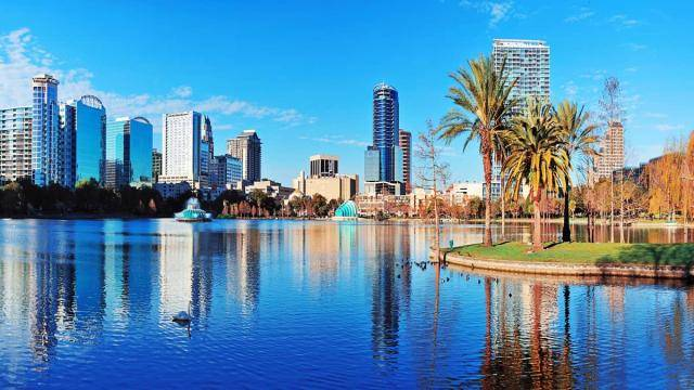 View of Lake Eola in Orlando, with buildings in the background reflecting in the water.