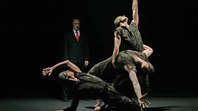 """Michael Tusnovec in a business suit and other dancers wearing army uniforms in Paul Taylor's """"Banquet of Vulture"""""""