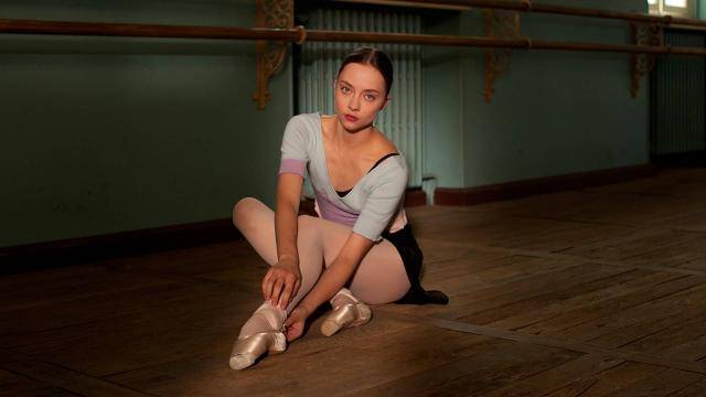 Dancer/actress Anastasia Shevtsova sitting on the classroom floor adjusting her pointe shoe.