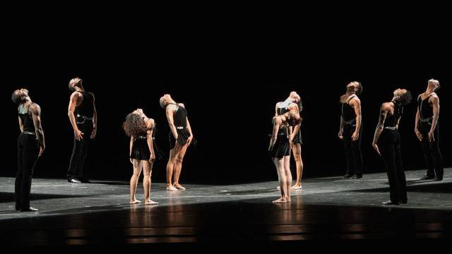 Group of dancers in black scattered across stage, standing upright, face to ceiling.