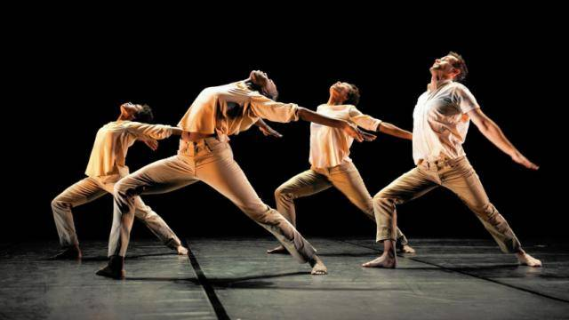 Four dancers wearing light colored pants and top, in a deep lunge forward and arching back.