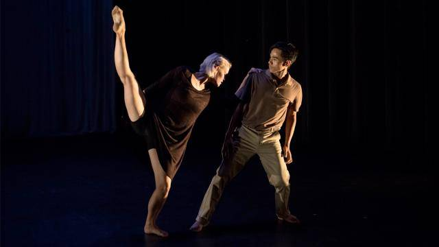 Blonde female dancer in a black dress, right  leg extended up, leaning to the left towards a male dancer in a brown shortsleeve shirt and kaki pants.