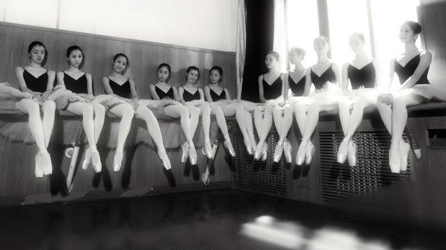 asian female ballet students in black leotard, white tutu and pointe shoes, sitting on a ballet barre along the wall