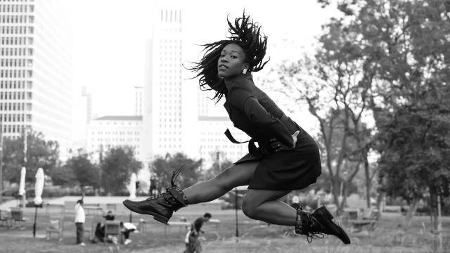 Dancer Jamila Glass in a black trench coat and boots, jumping against a city background