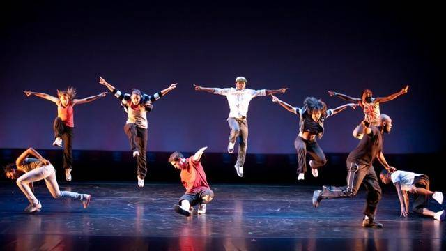 Dancers on stage, some jumping in the air while others are doing breakdance footwork on the floor.