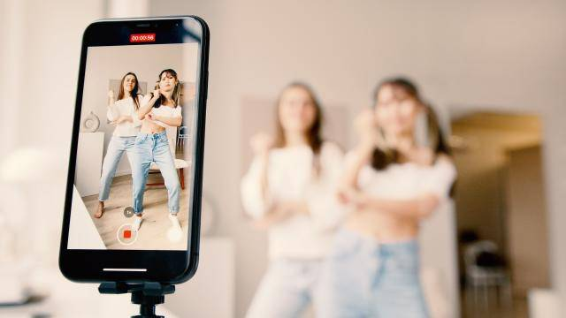 two young girls filming themselves dancing on a phone for social media