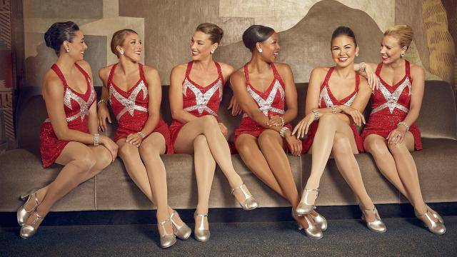 Six Rockettes wearing red sequin costumes, sitting on a beige couch, talking and laughing.