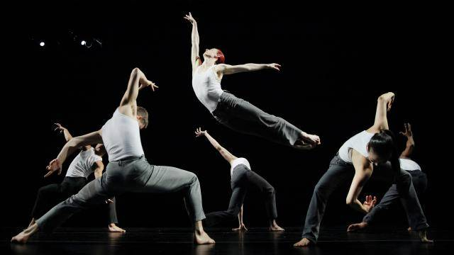 6 dancers in grey pants and white tops. One female dancer in the centre lifting by another dancing and showing a red apple.