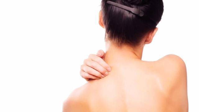 A young woman facing back and massaging her neck with one hand.