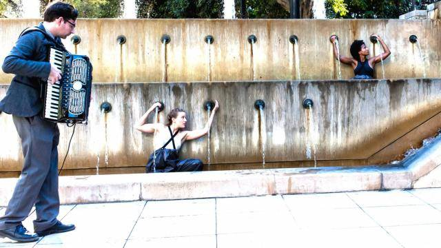 Two dancers from Heidi Duckler Dance performing in a water wall fountain, accompanied by a accordeonist