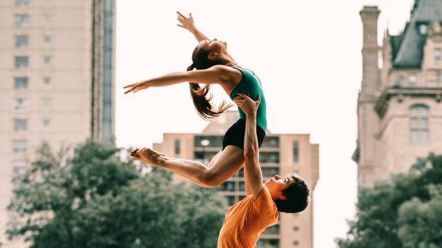 Female ballet dancer in a green leotard being lifted by a young male dancer, with buildings in the backdrop.