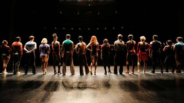 Back view of a line up of performers looking into the theatre house - from Every Little Step