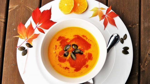 pumpkin soup in a white bowl and plate decorated with orange slices and fall color leaves