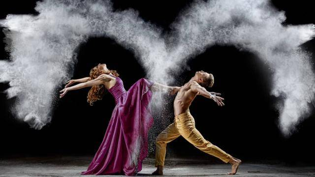 Female dancer placing her foot on a male dancer's chest, both arching back, arms opened, surrounded by white powder.