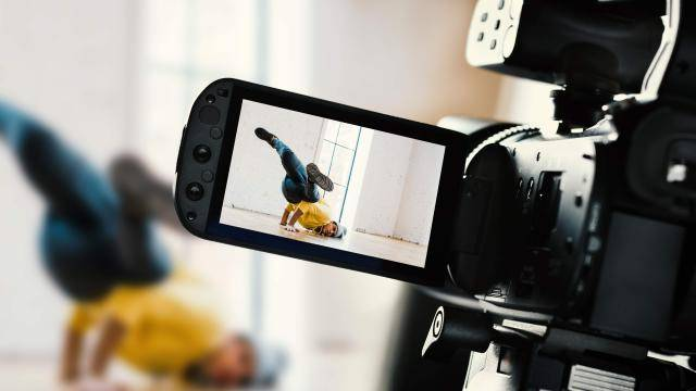 breakdancer with yellow sweatshirt being filmed on camera in a breaking pose