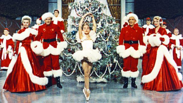 Ending scene of the movie White Christmas (1954), with a young dancer in white on pointe in front of a big Christmas tree.