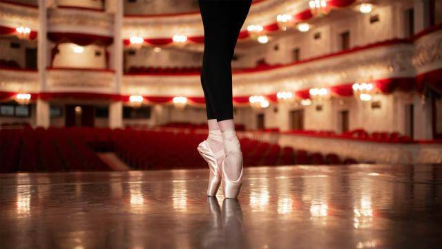 Close up of a ballerina's feet on pointe on a theatre stage.