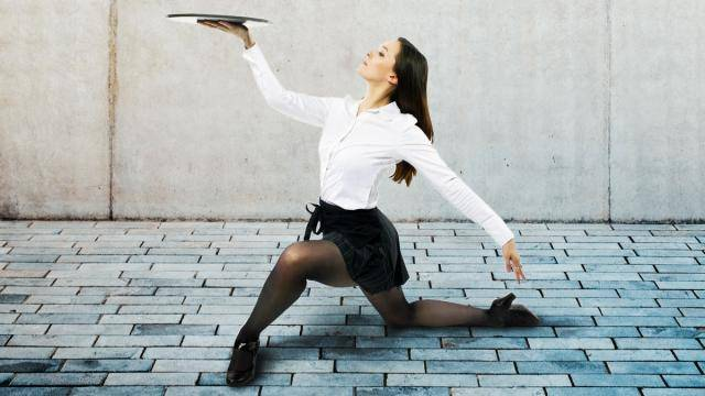 A dancer dressed as a waitress on one knee, holding a serving tray up.