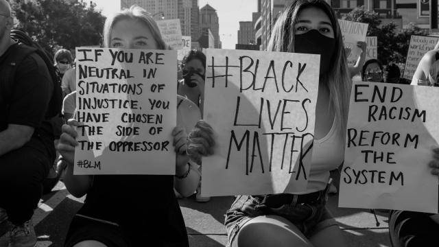Black Live Matters supporters kneeling in the street and holding written signs