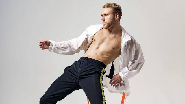 Aaron Czuprenski in an open white shirt and black pants, leaning back