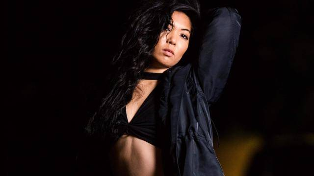 Tracy Takahashi in a black bra and black open blouse, arm overhead, on a dimly lit background